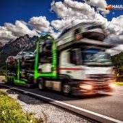 Truck trailer transports new cars rides on highway