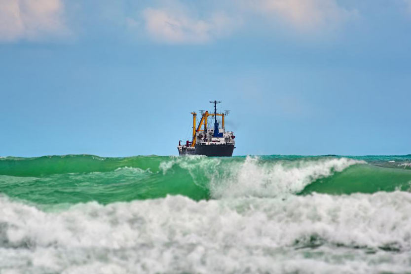 Waves with cargo ship in background