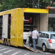 An enclosed tractor trailer transporting car